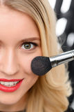 Professional make up is being applied. Blush spreading. Smiling young model in the process of blush applying and spreading stock photos