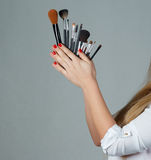 Professional make-up brush cosmetic in female hand beautician Stock Photos