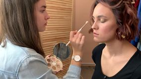 Professional make-up. Artist woman doing makeup and hairstyle to her client stock footage
