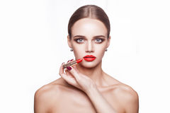 Professional makeup artist applies makeup for beautiful young woman with blue eyes and light brown hair style and perfect skin. Stock Photography