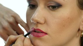 Professional makeup artist applying contour on lips of model. fashion industry cosmetics.  stock video