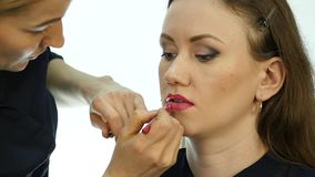 Professional makeup artist applying contour on lips of model. fashion industry cosmetics.  stock video footage