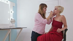 Professional makeup artist applying lipstick on lips of model stock video