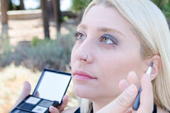 Professional makeup artist applying make up outdoor Royalty Free Stock Images