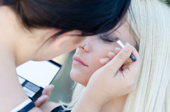 Professional makeup artist applying make up outdoor Royalty Free Stock Image