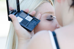 Professional makeup artist applying make up outdoor Royalty Free Stock Photography