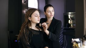 Professional makeup artist in black suit with pony tail applying cosmetic `s on model`s face with a large black make up. Brush. Young girl in black clothes in stock video footage