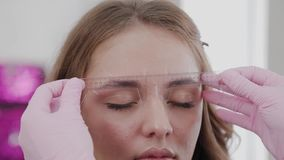 Professional makeup artist does eyebrow markup for client girl. Professional makeup artist does eyebrow markup for client girl stock video footage