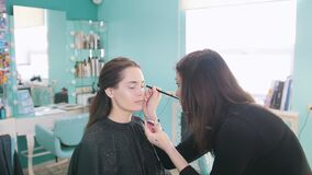 Professional makeup artist doing make-up with eye shadows stock video footage
