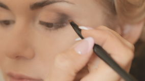 Professional makeup artist making eye makeup stock footage