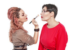 Professional makeup artist making makeup to a model isolated Stock Image