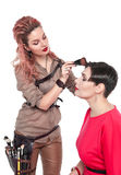 Professional makeup artist making makeup to a model  Stock Images