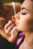 Professional makeup artist painting woman lips with brush Royalty Free Stock Images