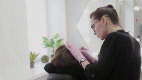 Professional makeup artist plucking eyebrows for client in beauty salon. Professional makeup artist plucking eyebrows for client in beauty salon stock footage
