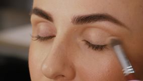 Professional makeup artist. Applies a brush to the upper eyelid of a beautiful girl with a brush. Client woman in beauty salon doing makeup close-up stock video footage
