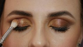 Professional makeup artist. Applies a brush to the upper eyelid of a beautiful girl with a brush. Client woman in beauty salon doing makeup close-up stock video