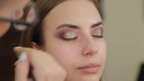 Professional makeup artist puts eye shadow on a client of a beauty salon. stock footage