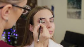 Professional makeup artist puts eye shadow on a client of a beauty salon. stock video footage