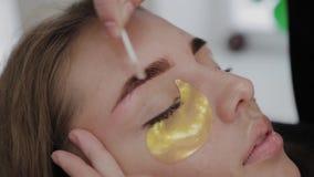 Professional makeup artist removes eyebrow paint to client. Professional makeup artist removes eyebrow paint to client stock footage