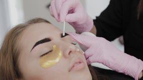 Professional makeup artist removes eyebrow paint to client. Professional makeup artist removes eyebrow paint to client stock video