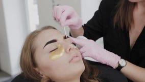 Professional makeup artist removes eyebrow paint to client. Professional makeup artist removes eyebrow paint to client stock video footage