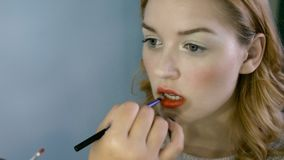 Professional makeup artist working with beautiful young woman stock footage