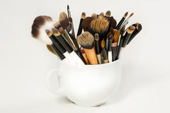 Professional makeup brush in a white cup. White background, shadow Stock Photo