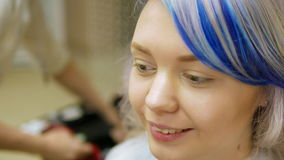 Professional makeup person a young girl with blue hair. stock video footage