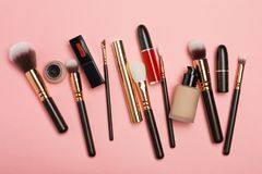 Professional makeup products with cosmetic beauty products, blushes, eye liner, eye lashes, brushes and tools on pink background stock photos