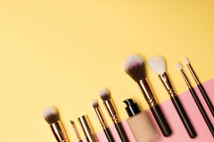 Professional makeup products with cosmetic beauty products, blushes, eye liner, eye lashes, brushes and tools on pink and yellow stock photo