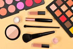 Professional makeup products with cosmetic beauty products, eye shadows, pigments, lipsticks, brushes and tools on beige. Background. Space for text or design royalty free stock photo