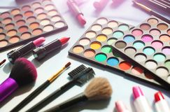 Professional make up set: eyeshadow palette, lipstick, make-up brushes and many cosmetics close up. Film and flare effect Stock Image