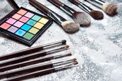 Professional makeup tools on white wooden background. Highlighter, sculptor, powder for sculpting, kabuki brush , brush for blush, brush for sculpting, fixture Stock Image