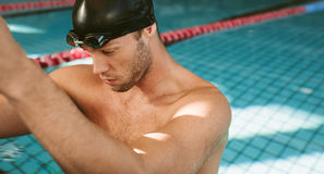 Professional male athlete resting on the edge of pool. Close up shot of professional male athlete resting on the edge of pool. Young man in swimming pool Stock Photos
