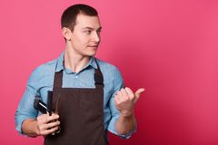 Professional male barber holds electric razor, scissors and comb, dressed in shirt and apron, points with thumb aside, shows royalty free stock photo