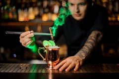 Professional male bartender adding to a cocktail with dried orange a smoked cinnamon with tweezers. Professional male bartender adding to a cocktail in the stock photography