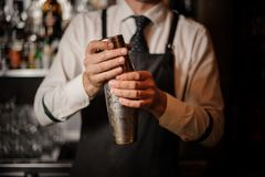 Professional male bartender holding a steel shaker. Ready to prepare a fresh cocktail at the bar counter stock images