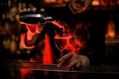 Professional male bartender pouring a smoke into the cocktail glass from the steel shaker royalty free stock photography