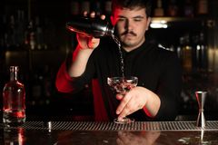 Professional male bartender pouring a transparent alcohol into the cocktail glass from the steel shaker royalty free stock image