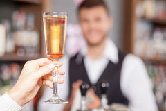 Professional male bartender is serving customer in Stock Photography