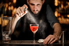Professional male bartender spraying on the delicious transparent red cocktail in the glass. On the bar counter in the blurred background stock images