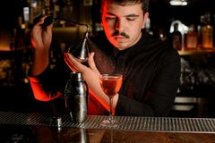 Professional male bartender spraying from the diffuser on the delicious cocktail in the glass stock image