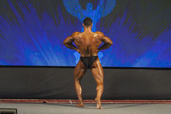 Professional Male Caucasian Bodybuilder Performing on Stage. Bac Stock Photography