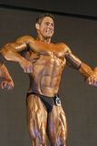 Professional Male Caucasian Bodybuilder Performing on Stage. Stock Photography