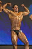 Professional Male Caucasian Bodybuilder Performing on Stage. Stock Photos