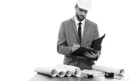Professional male constructionist writing on his clipboard. Construction professional. Black and white shot of a businessman architect wearing protective helmet Stock Image