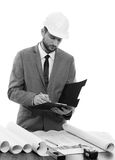 Professional male constructionist writing on his clipboard. Noting carefully. Monochrome shot of a professional constructionist writing on his clipboard Royalty Free Stock Photos