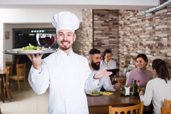 Professional male cook showing country restaurant. To visitors Royalty Free Stock Image