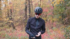 Professional male cyclist in black helmet and glasses puts on cycling gloves before training on bike. Cycling man preparing for wo. Rkout outdoor in fall city stock video
