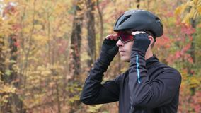 Professional male cyclist in black sports apparel and helmet preparing for training in autumn park and puts on glasses. Cycling tr. Aining in fall park. Side stock video